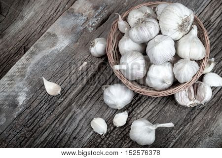 Fresh organic garlic in wicker basket on rustic table