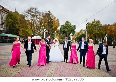 Group Of Wedding Friends Walking On Line At Square
