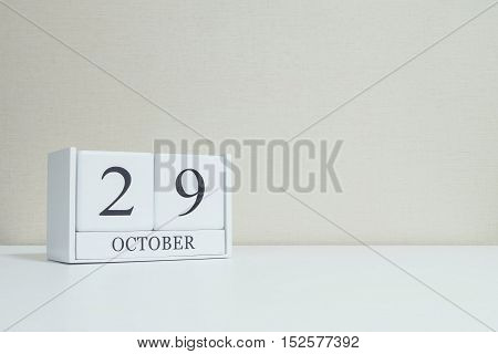 Closeup white wooden calendar with black 29 october word on blurred white wood desk and cream color wallpaper in room textured background with copy space selective focus at the calendar