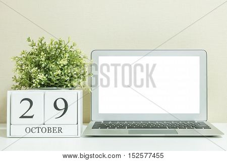 White wooden calendar with black 29 october word with white blank space at center of computer notebook on white wood desk and cream wallpaper textured background selective focus at the calendar