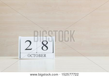 Closeup surface white wooden calendar with black 28 october word on blurred brown wood desk and wood wall textured background with copy space selective focus at the calendar