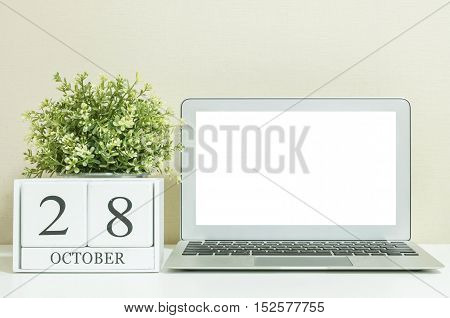 White wooden calendar with black 28 october word with white blank space at center of computer notebook on white wood desk and cream wallpaper textured background selective focus at the calendar