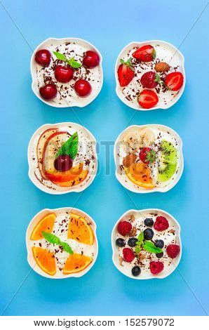 Six different yogurts with fresh fruits, berries displayed vertically in 2 rows of 3 pieces on light blue background. Six yogurts with fresh fruits and berries. Vertical. Top view.