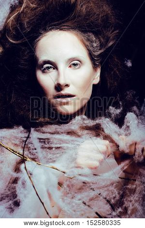 beauty woman with creative make up like cocoon, halloween celebration creepy web