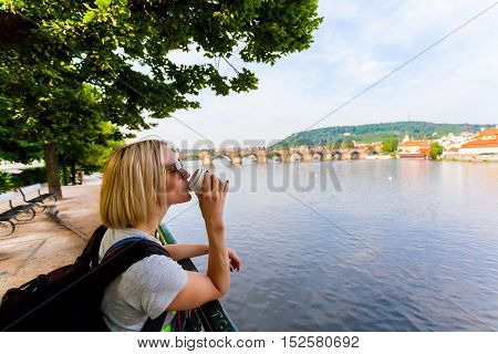 Female traveler drinking coffee and enjoying a panoramic view of the Vltava River and the Charles Bridge in Prague.