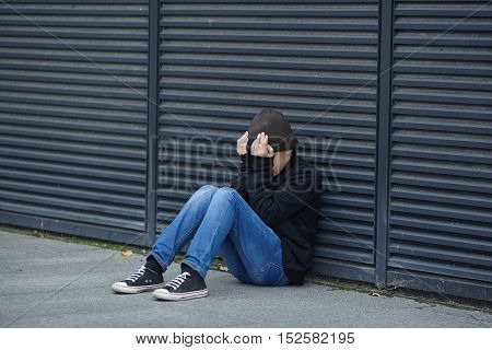 young homeless boy sleeping on the street poverty city
