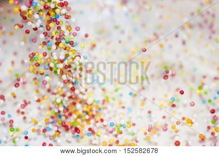 Colourfull small candy dropping on the white background