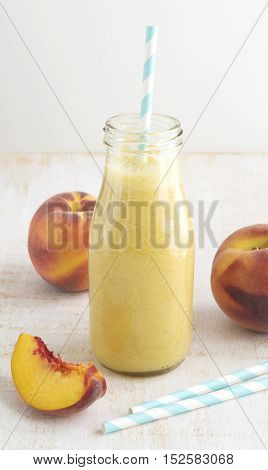 Peach fruit smoothie in glass bottle and paper straws on wooden table. Healthy lifestyle selective focus vertical