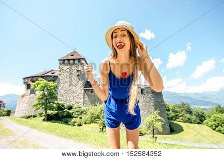 Vaduz, Liechtenstein - July 01, 2016: Young female tourist visits Vaduz castle in the capital of Liechtenstein. This castle is the palace and official residence of the Prince of Liechtenstein