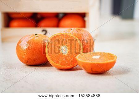 Ripe tangerine in wooden box on white wooden floor.