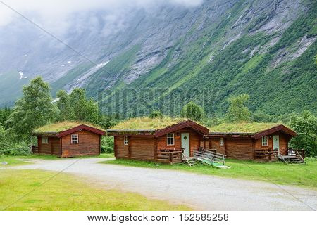 Norwegian wooden houses with grass on the roof at the foot of the mountain