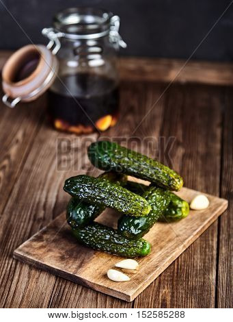 A stack of pickled cucumbers in soy sauce and rice vinegar on cutting board on wooden table, cloves of garlic near it. Crunchy and salty pickles. Chinese recipe. Selective focus, closeup shot