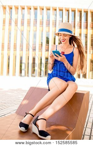 Young woman in blue dress using phone outdoors sitting on the modern bench on the wall background