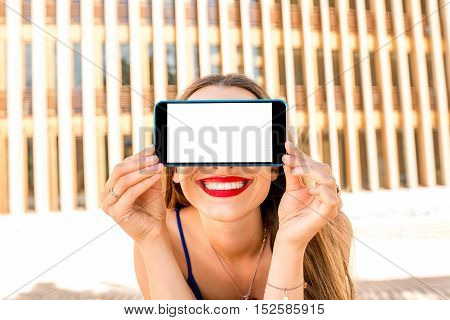 Close-up portrait of smiling woman holding phone with white screen to copy paste on the modern wall background