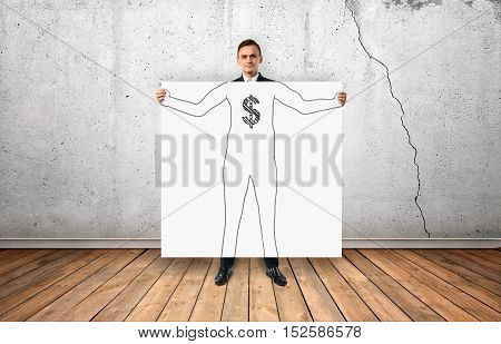 Front view of businessman holding big white poster with his drawn silhouette and dollar sign on his chest on the background of concrete wall. Making money. Management and administration.