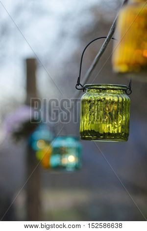 Hanging handmade colourfull candle jars at the garden party