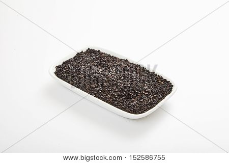 Black sesame in white rectangular saucer. White isolated background. Perfect seasoning for salads, desserts, garnishes and main dishes. Closeup shot, selective focus
