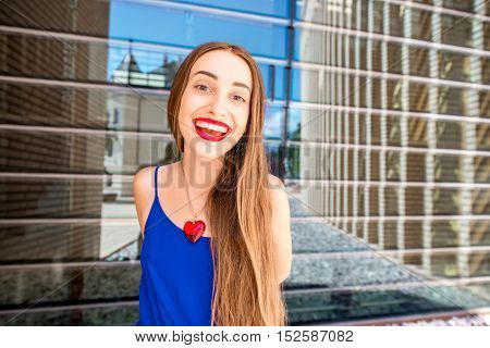 Portrait of a young smiling woman outdoors on the modern glass wall background