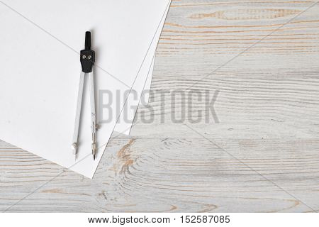 Compass on white paper in top view with copy space on the right side. Workplace of architect, constructor, designer. Start a new project. Construction and architecture. Tools for drawing.