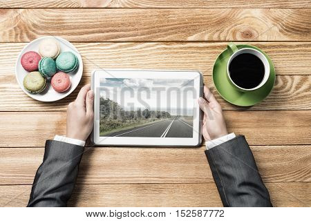 Top view of businesswoman sitting at wooden table and using tablet pc