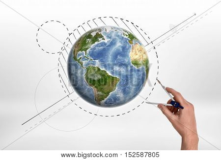 Man's hand holding engineering compass measures the distance near Globe. Formation of a world map. Engineering works. Measuring process. Elements of this image are furnished by NASA.