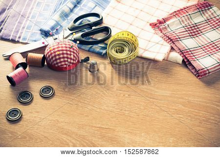Old scissors buttons threads material on wooden table