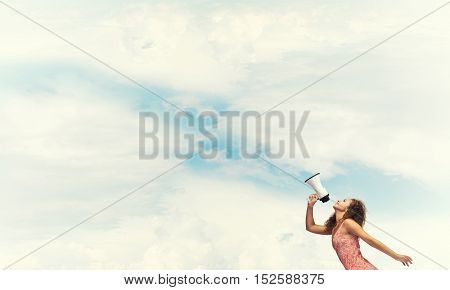 Young woman shouting in megaphone with blue sky background