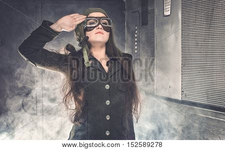 Woman soldier in World War II uniform. Standing in smoke in old elevator.