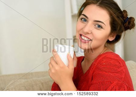 Portrait of young brunette woman sitting on couch in her living room and drinking coffee or tea