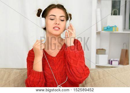 Woman listening music in headphones sitting on sofa in room