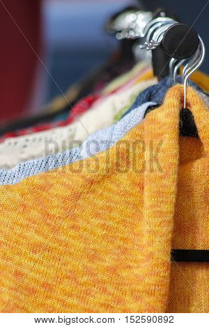 Half of knitted colourfull handmade sweaters on metal hangers
