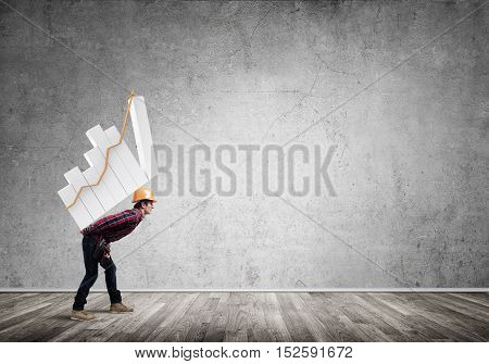 Young man builder carrying growing graph on his back