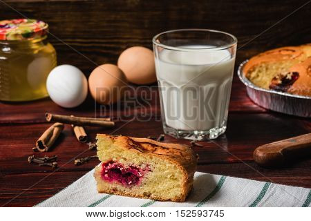Sweet breakfast with cherry cake and glass of milk and ingredients lie on the table.