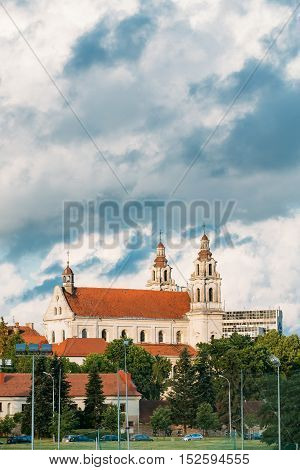 Vilnius, Lithuania. Side View Of The Church Of St Philip And St Jacob, The Ancient Roman Catholic Church With Monastery And Red Tile Roof Against The Background Of Scenic Blue Cloudy Sky In Summer.