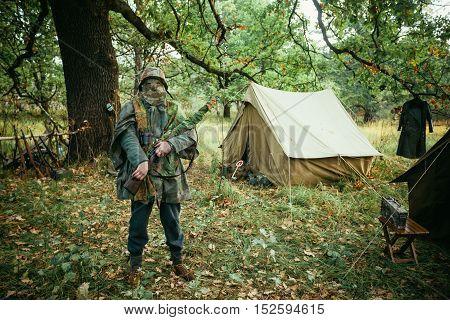 Hidden unidentified re-enactor dressed as World War II german wehrmacht sniper soldier in forest.