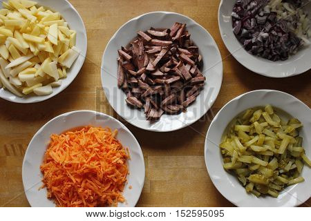 Different cutted soup ingredients in white plates