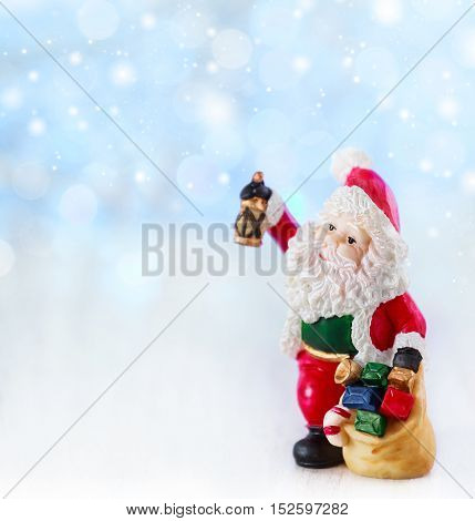 Merry christmas card with Santa Claus figurine. Lights background with space for text. Winter holidays. Xmas theme