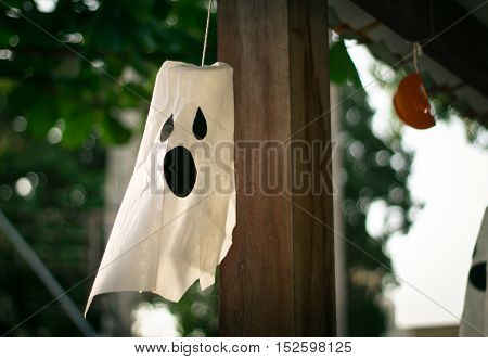 Halloween white ghost decoration hanging outdoors at daytime