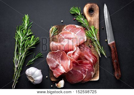 prosciutto on board on dark background, view from above