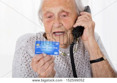 Portrait Of Senior Woman Giving Credit Card Details On The Phone