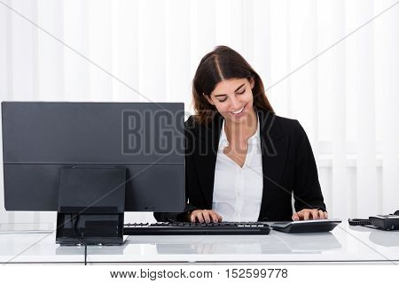 Successful Businesswoman Using Calculator While Working In Office
