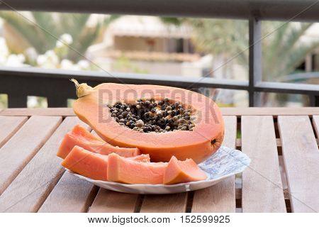 Papaya slices on a plate on the palms background