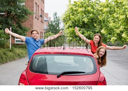 Excited Happy Family Looking Out Of A Car In City