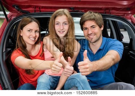 Cheerful Family Sitting Inside The Trunk Of Their Car Showing Thumbs Up