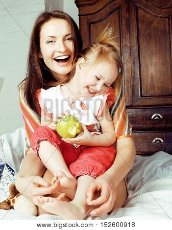 mother with daughter together in bed smiling, happy family close up, lifestyle people concept, cool real modern family at home