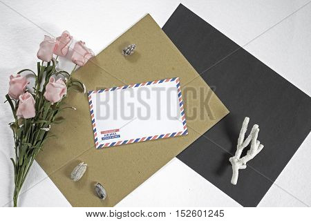 Composition with letter and pink flowers on white background. Sea holiday or travel souvenir on table. Photo backdrop with white black and craft paper. Mockup image