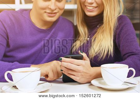 Young man and woman looking at the phone, read SMS or watch photos.