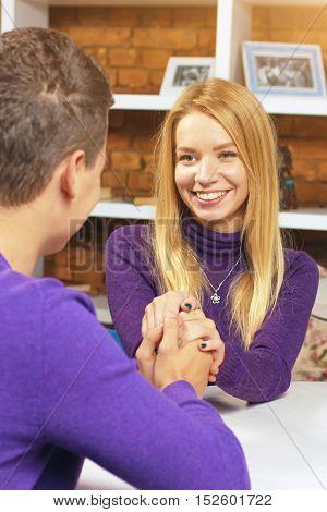 Beautiful girl looks at the boy and holding his hand. Romantic otnasheniya men and women.