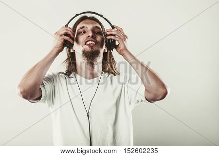 Music and sound. Young long haired happy man with headphones listening sounds. Communication.