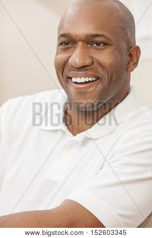 A happy handsome African American man with perfect teeth in his thirties sitting at home